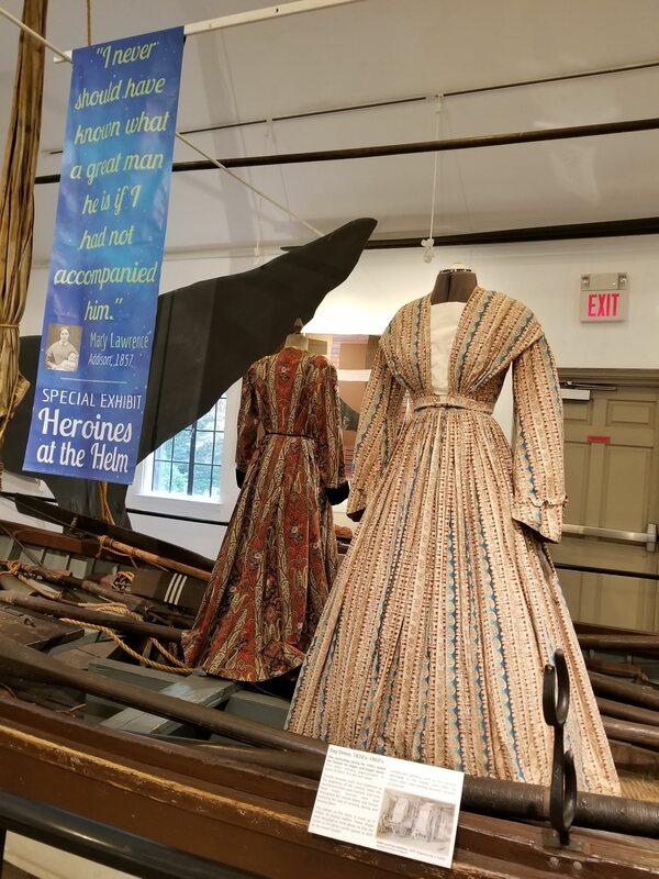 View of formal 19th century dress mounted on female form inside historic whaleboat.