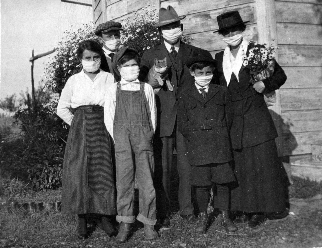 A caucasian family of three adults, three kids, and a cat pose outdoors of their home wearing white masks in a black and white photo