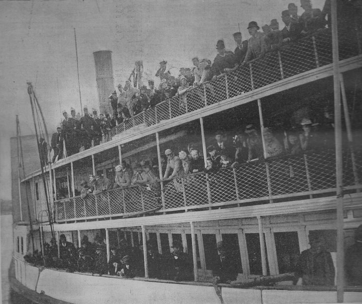 Black and white photograph of the side of a crowded ship at dock, showing three tiers of people