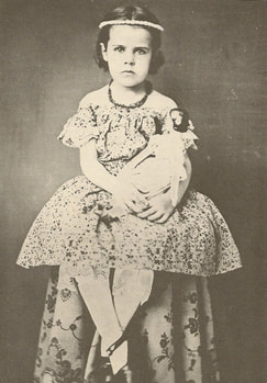 Uncolored photo of young girl about 5 years old sitting with dress and necklace, legs crossed at the ankle, and somewhat serious staring face, holding a doll