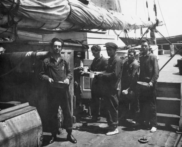 Black and white photo of whalers standing in line with plates on deck