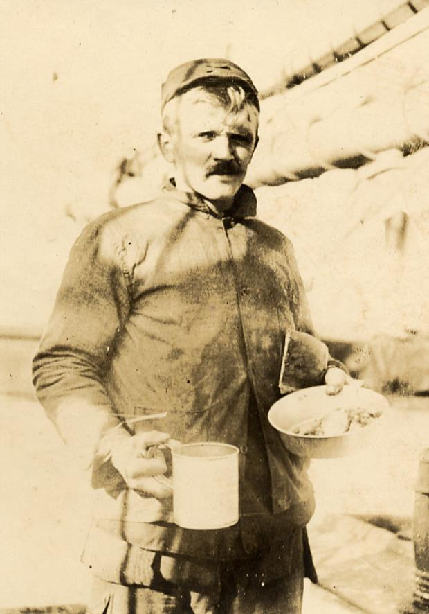 A whaler faces the viewer holding a tin cup and plate filled with food.